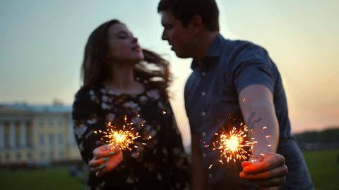 The couple, girl and guy, kissing with bengal light sticks Footage
