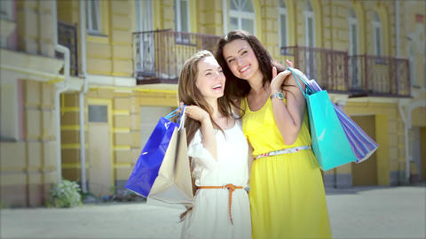 Two cheerful girls walking boutiques back to us then turn around to face us Footage