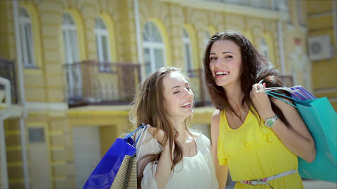 Two cute girls girlfriends happily posing with trendy shopping while shopping Footage