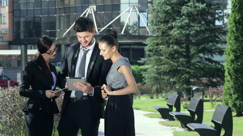 Company of three business people discussing a business deal on outside the Footage