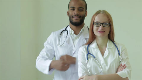 Two doctors put her arms and smiling at the camera Live Action