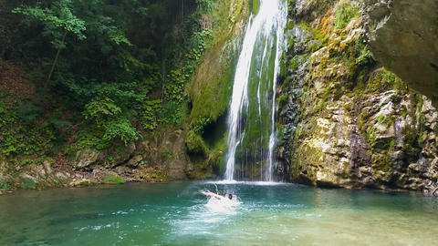 Brave man swimming towards waterfall, cooling and refreshing in its spatter Footage