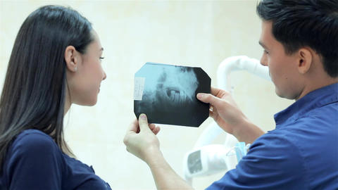 Dentist shows a patient x-rays of the teeth in the dental office Live Action