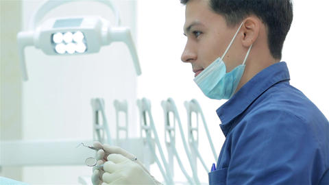 Dentist holding a dental instrument in his hands Live Action