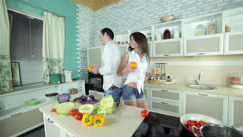 Panorama kitchen with a couple who hold orange juice and oranges Live Action