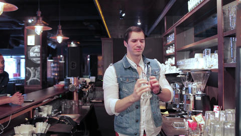 The bartender checks the purity of the glass and takes a drink two cheerful Live Action