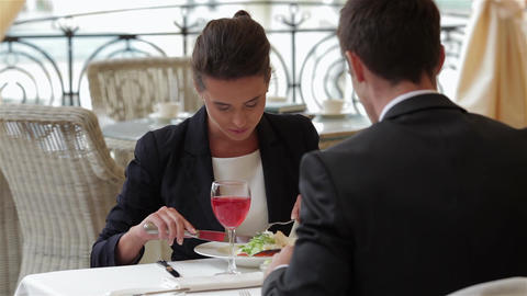 Businesswoman eating with a businessman Footage