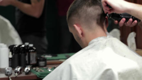 Young stylish tattooed barber cutting hair of a young man at barbershop Live Action