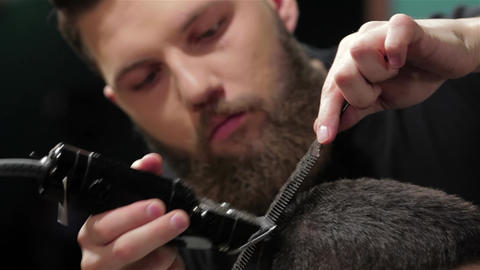 Men's hairstyling and haircutting with hair clipper in a barber shop or hair Live Action