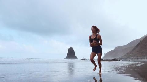 Running woman outdoors beach run. Atlantic ocean Live Action