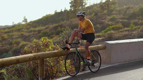 Wide angle tracking shot of a fit male athlete riding bicycle on long flat road Footage
