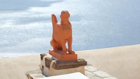 Clay statue of Greek sphinx on Santorini island against blue sunlit sea, tourism Footage