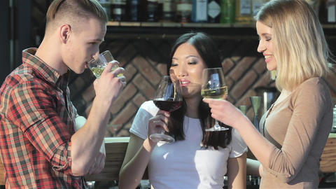 Man drinks beverages with two girls at the bar Live Action