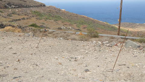 Coastal highway with cars running, hill with donkeys tied up to pole, contrast Footage