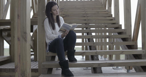 Beautiful woman reading outdoors on stairs – 4K Stock Video Footage
