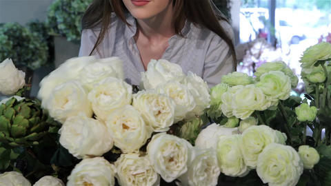 Female florist looks at white roses at flower shop Footage