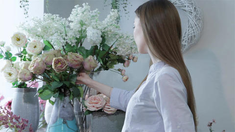 Female florist arranges flowers in vases at flower shop Live Action
