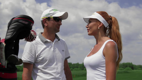 Instructor ask question to the female player about golf Live Action