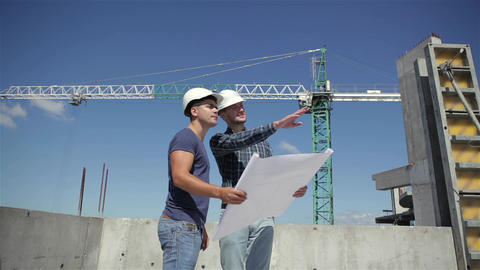 Construction manager points at the plan of building under construction Footage