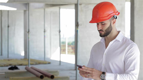 Construction engineer talking on the phone at the building under construction Footage