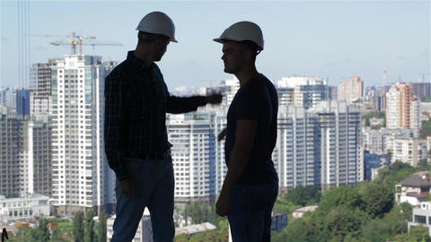 Two builders look at the landscape of high buildings Footage
