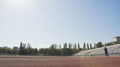 Professional athlete running at stadium, training hard to achieve sport success Live Action