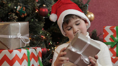 Little boy shakes the christmas gift box Live Action