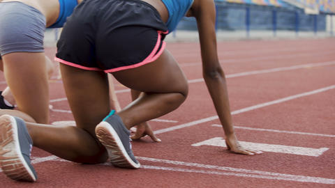 Multiracial girls getting to crouch start, running after command, way to success Live Action
