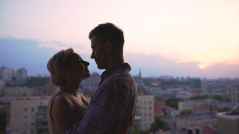 Beautiful couple basking in embraces, admiring sunset from roof of high building Live Action