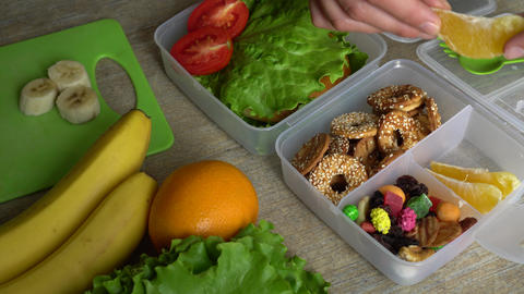Healthy lunch boxes with sandwich, fresh vegetables, fruits and nuts Live Action