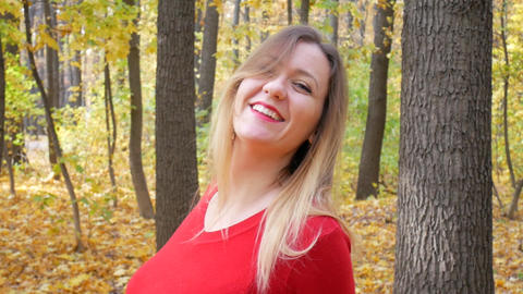 Cute woman rotates and smiling at park in autumn Footage