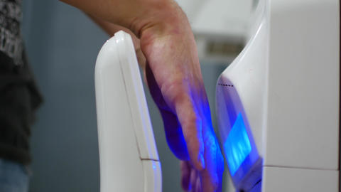 The man dries his hands under a stream of hot air. Hand dryer Footage