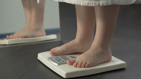 Extra weight, fat female in bathrobe stepping on scales to check diet results Live Action
