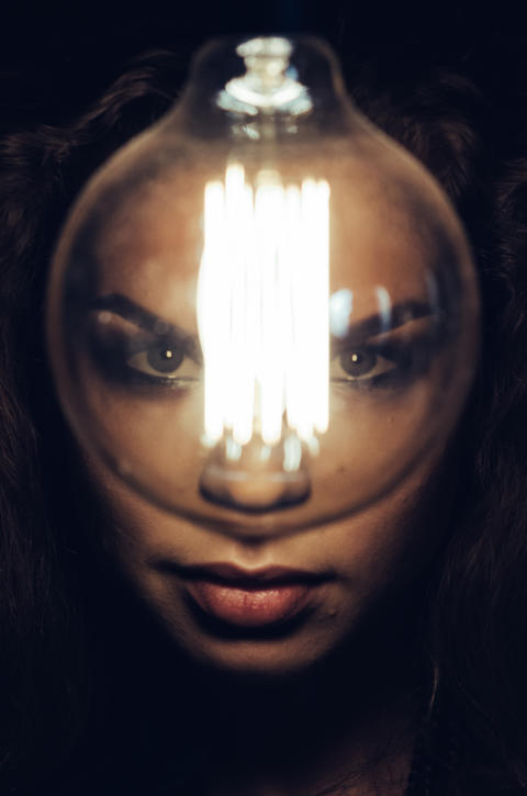 Mysterious photo of woman with light bulb. Portrait in the dark. Dangerous girl Photo