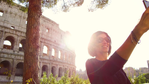 woman takes a selfie in front of the majestic Colosseum in Rome Live Action