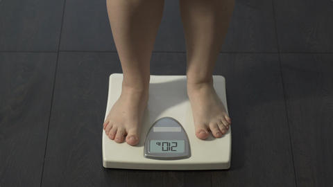 Extra body weight, female stepping on scales at home to check diet result, obese Live Action