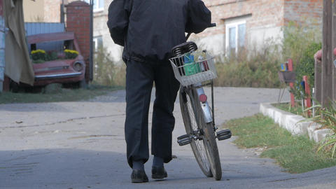 Man walks with old rusty bike in countryside. concept of poverty, tramp Footage