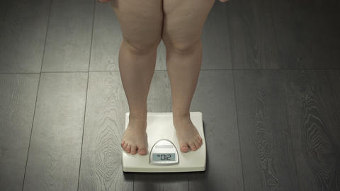 Female with extra weight stepping on bathroom scales, health disorder, obesity Footage