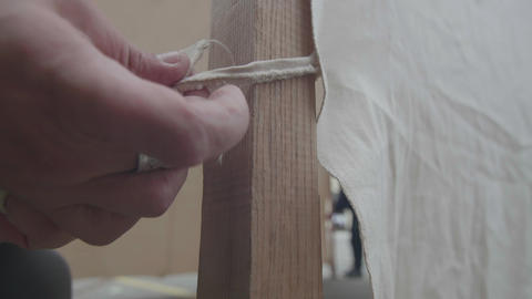 Hand of a man who binds the bonding of the material to the wooden pole 84a Live Action
