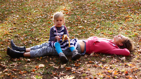 Beautiful mom and cute kid lying on the grass in autumn park. Daughter sits on Footage