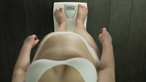 Woman with extra weight standing on bathroom scales, unhealthy index, problems Live Action