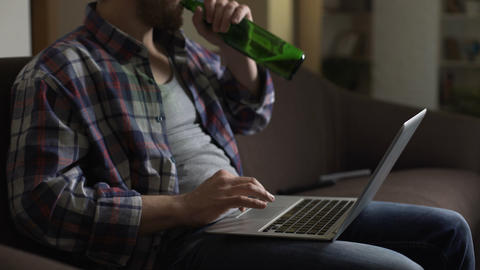 Untidy man on sofa using laptop and drinking beer, browsing internet, loneliness Live Action