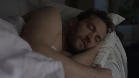 Adult bearded man sleeping in bed, exhausting day, sound sleep and night rest Footage