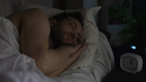 Bearded man sleeping on sofa bed, clock standing on night table, late night rest Footage