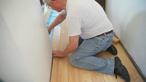 Man installs laminate floor DIY Footage