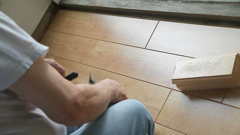 Homeowner fitting laminate floor pieces together Footage
