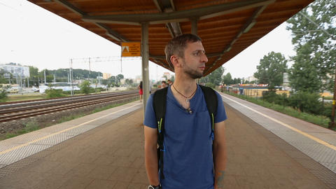 Male passenger waiting for delayed train to arrive, looking ahead nervously Live Action
