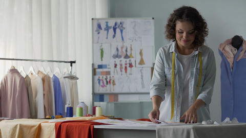 Fashion designer reviewing sketches thinking about her new creation, inspiration Footage