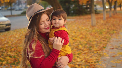 Happy young mother playing with her little baby girl on sunshine warm autumn day Footage