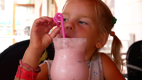 Cute little girl in cafe with milkshake cocktail Live Action